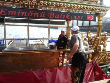 """Chef on board hands over a freshly grilled fish fillet at one of the fish quayside """"restaurants"""" in Istanbul."""