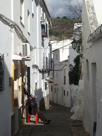 And old man rests in a sunny spot on a narrow street in Casares.