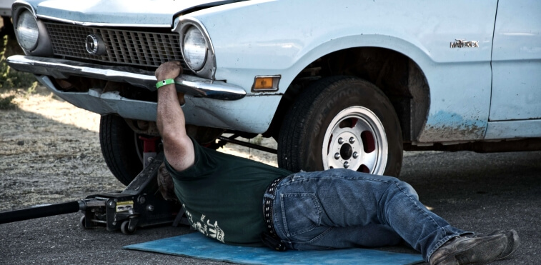 Auto mechanic inspecting the underside of a car