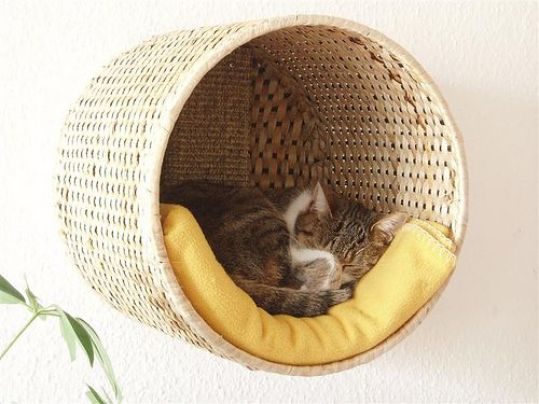 Mount a wicker basket on your wall with some comfy bedding inside to create a cozy nook for kitty to sleep in. | www.themeowplace.com