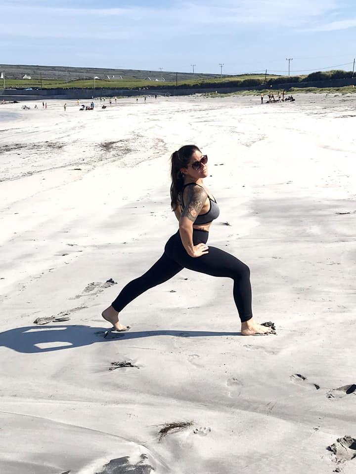 Woman doing a lunge in the sand at Kilmurvey Beach on the island of Inis Mor in Ireland.