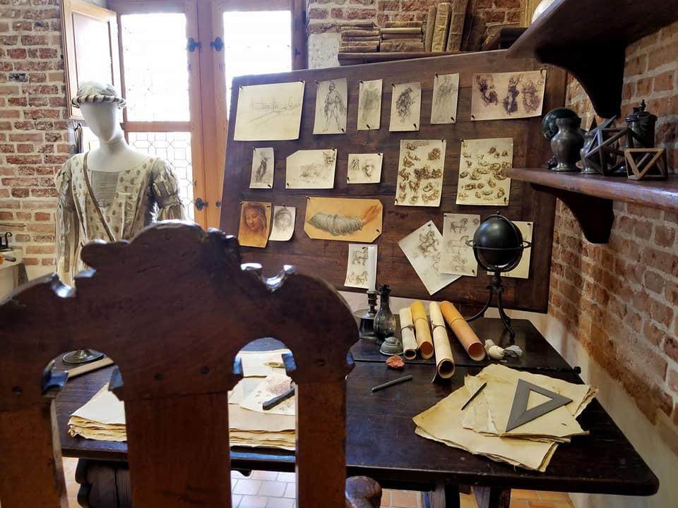 Leonardo da Vinci's workshop, desk and pinned drawings to a board.