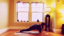 Woman in lizard pose with the top of back foot pressed down into the floor and knee lifted (yoga pose)