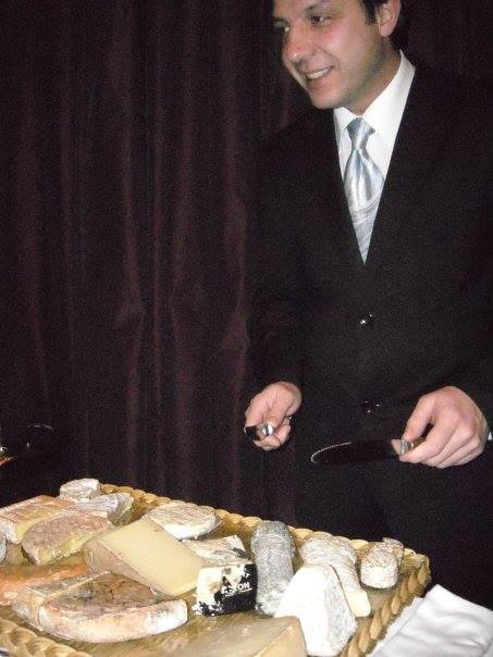 Waiter at fancy restaurant presenting a cheese plate in Paris.