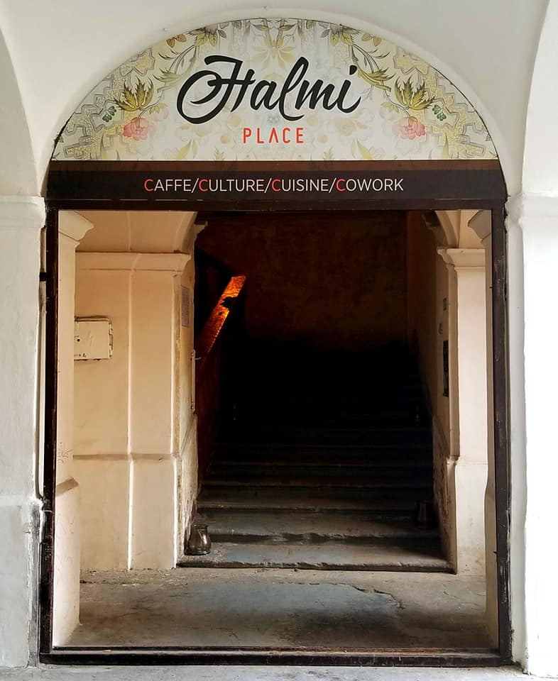 Entrance to Halmi Place, a coffee shop/co-op in Kosice, Slovakia. There are two double doors that offer a wide entrance. On top of the doors it says 'Halmi Place' written in cursive.