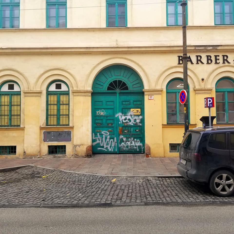 Bright yellow building with teal doors in Kosice, Slovakia. There is white graffiti all over the arced door. The street in front of the building is cobblestone and there is a sign that says 'BARBER' in the upper right hand corner. There is the rear portion of a dark vehicle parked on the street on the right with a street pole behind it.