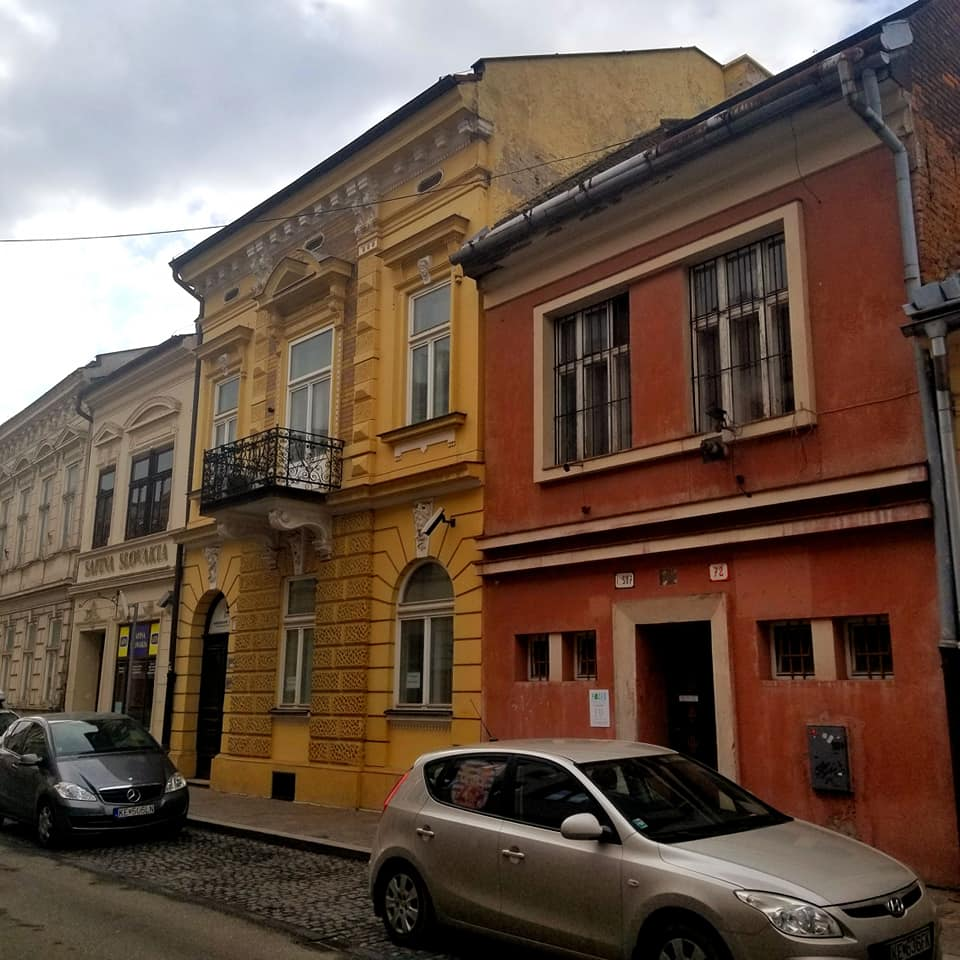 Looking down the street in Kosice Slovakia. There are cars lining the cobblestone road with three buildings visible. The farthest is cream colored, then deep mustard yellow, and then a red building.