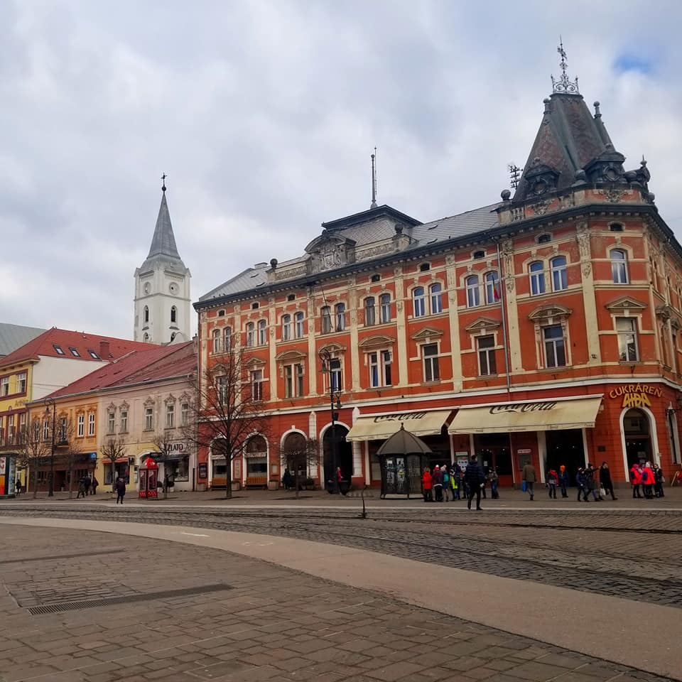 Exterior of a red building in Kosice, Slovakia. The building has cream colored trim and a black roof. There are cream colored awnings in the front of the building. The street in front of the building is made of cobblestone. There are a few people immediately in front of the building.
