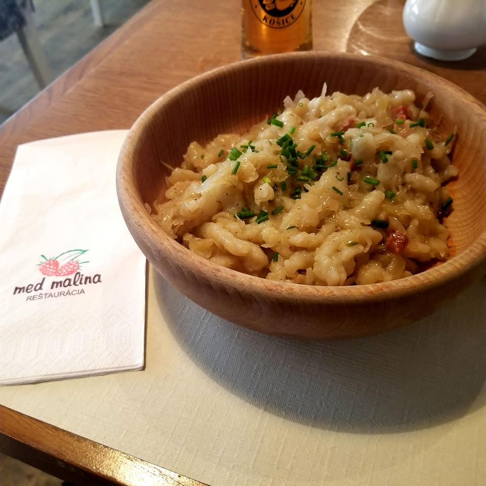 Traditional Eastern Slovak dish of potato dumplings with roasted bacon and sour cabbage served in a bowl. Next to the bowl is a napkin with the 'Med Malina' logo on it with a beer in the background.