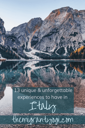 photo of lago di braies in South Tyrol, Italy. There is text that reads '13 unique and unforgettable experiences to have in italy' and beneath that text is more text that reads 'themigrantyogi.com'
