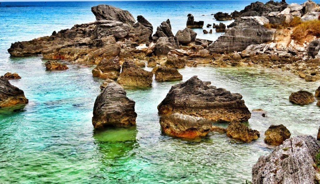 Jutting limestone formations coming out of the water at Tobacco Bay, Bermuda