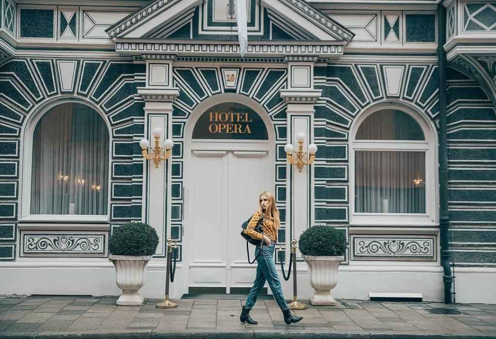 Woman walking down the sidewalk in front of the Hotel Opera in Munich, one of the most iconic and instagrammable places in Munich.