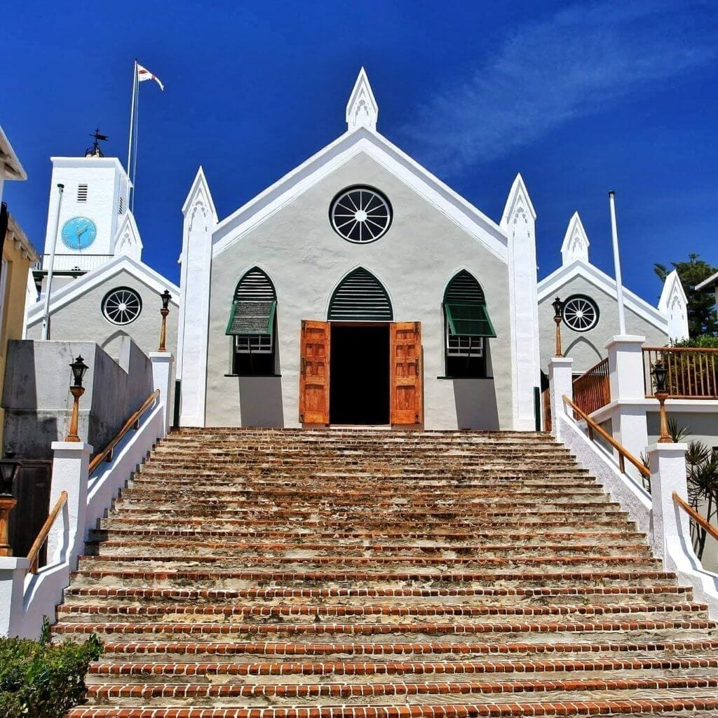 Picture looking up the steps of St. Peter's Church in St. George's, Bermuda.  The church is the oldest continuously used Protestant church in the New World.  The wooden double doors are open, and the skies are a deep blue with wisps of clouds dotting the sky.