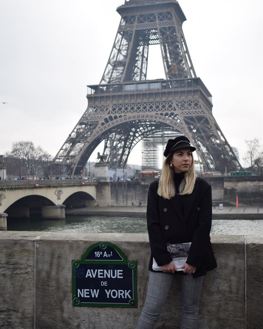 Woman standing beside Avenue de New York sign in front of the Eiffel Tower