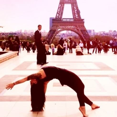 Barefoot woman doing yoga in front of Eiffel Tower at Trocadero
