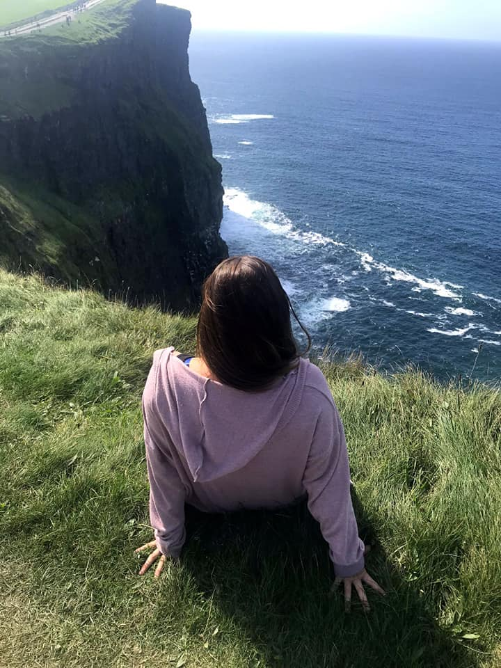 Woman sitting on the edge of the Cliffs of Moher