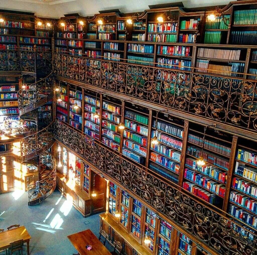 Colorful walls of ornate carved bookshelves at a library in Munich, Germany.