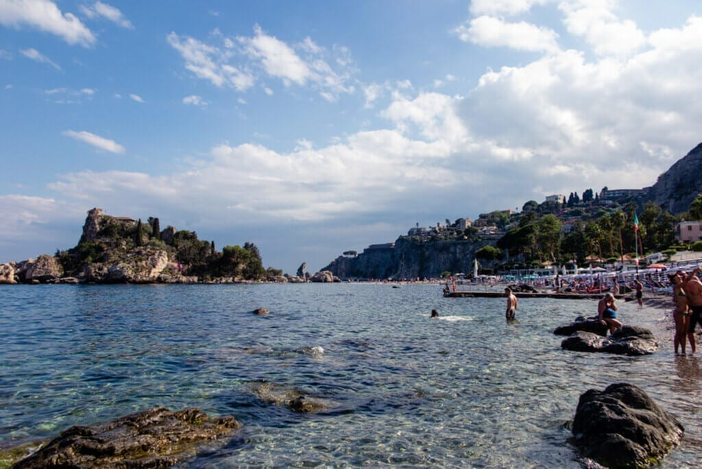 Many people gathered on a rocky beach in Sicily with blue skies and some clouds, crytal waters.