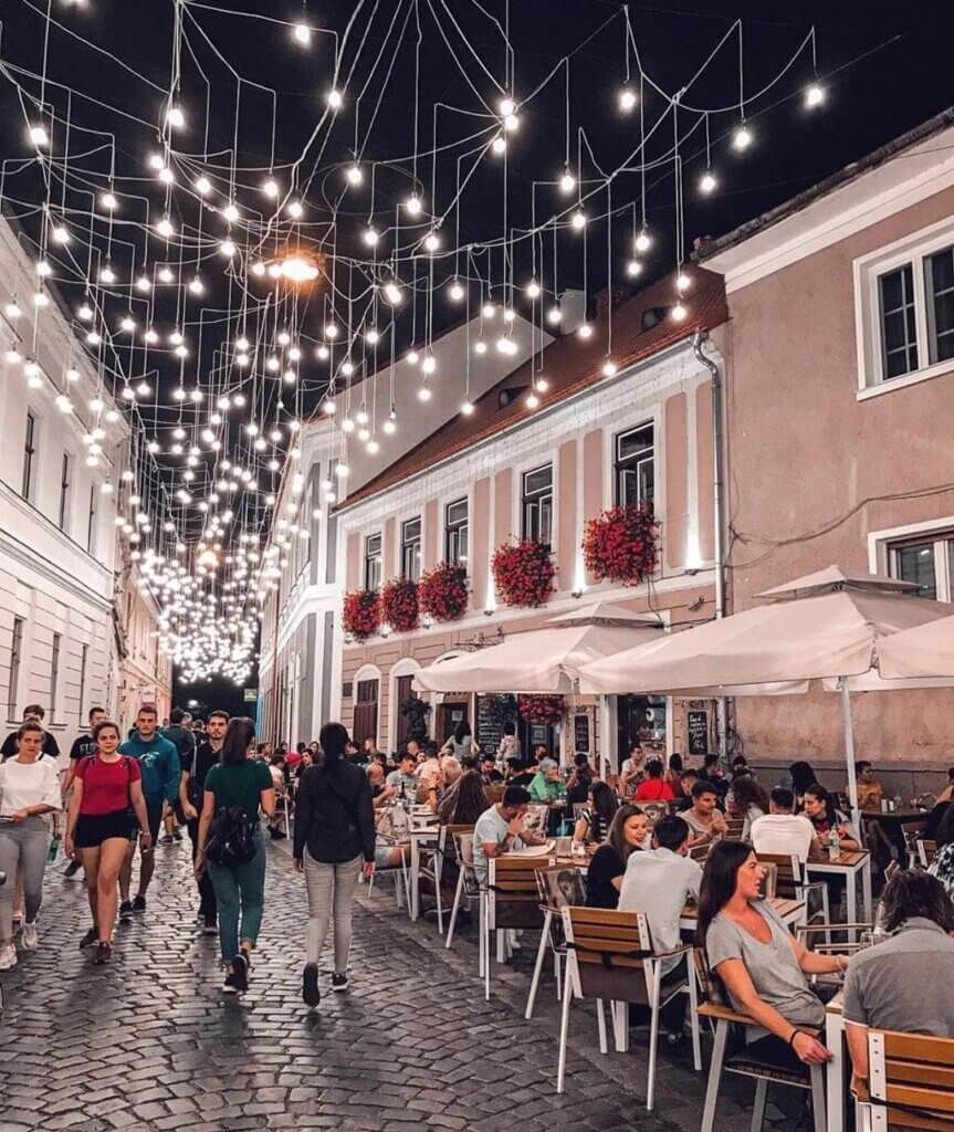 Museum Square in Cluj-Napoca, Romania with the overhead strung lights glowing on the people walking on the street below.