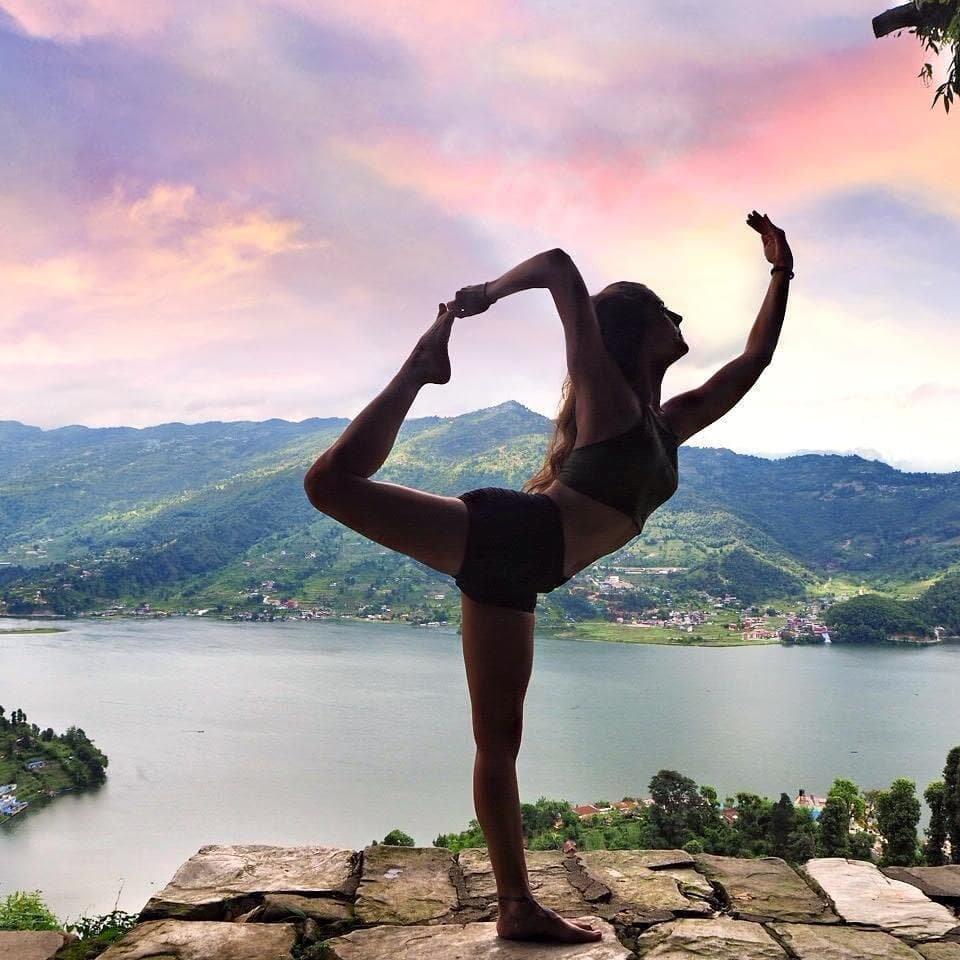 Woman doing dancer pose next to water during sunset.