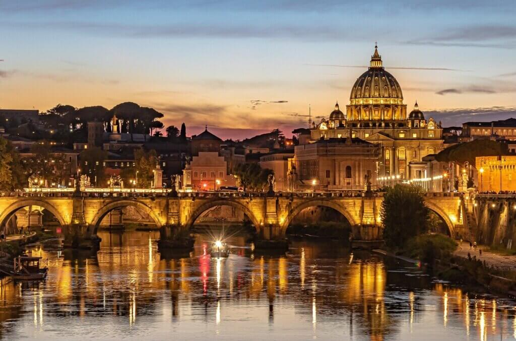 Bridge and ancient buildings in Rome as seen at dusk with lights reflecting off the Tiber river.