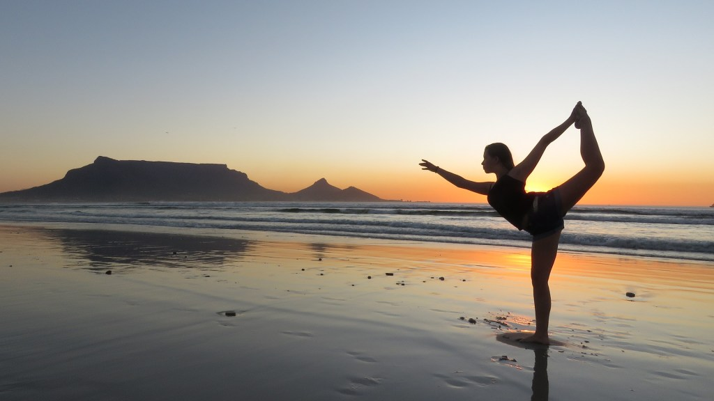 Woman doing dancer pose on a beach during sunset.