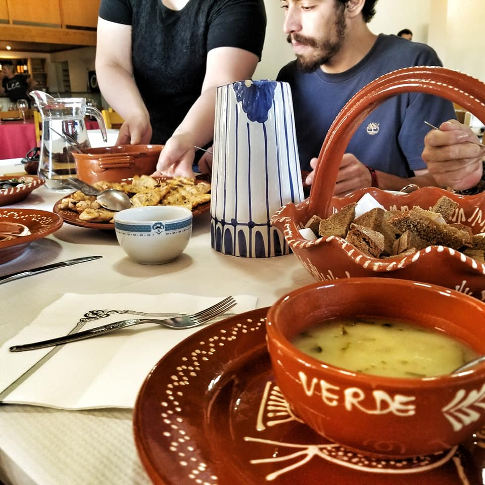 People gathered around a table to eat Portuguese food in the Peneda-Geres region of Portugal.
