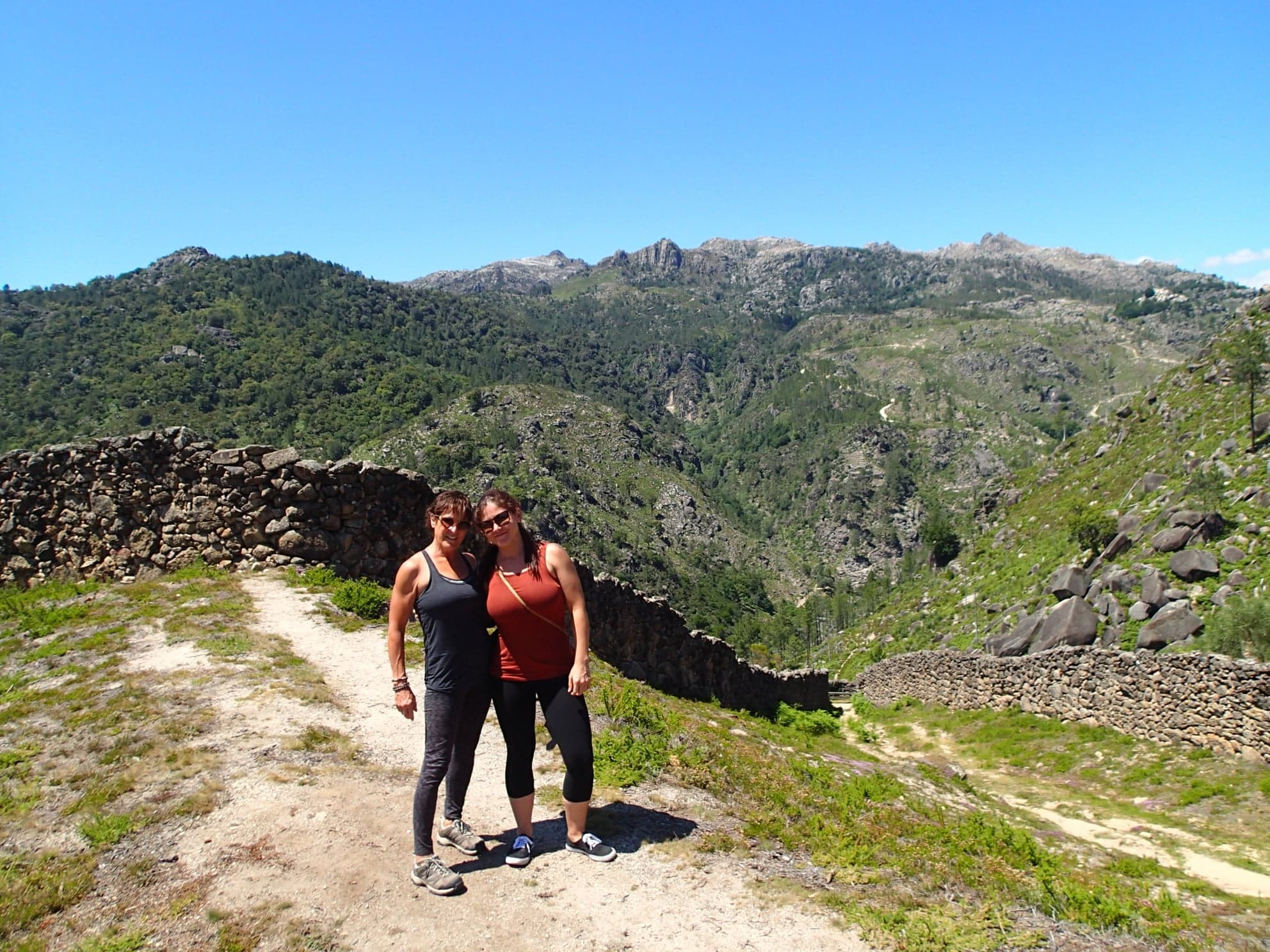 Two woman standing at the formation of where a wolf trap in Portugal is for villagrs.
