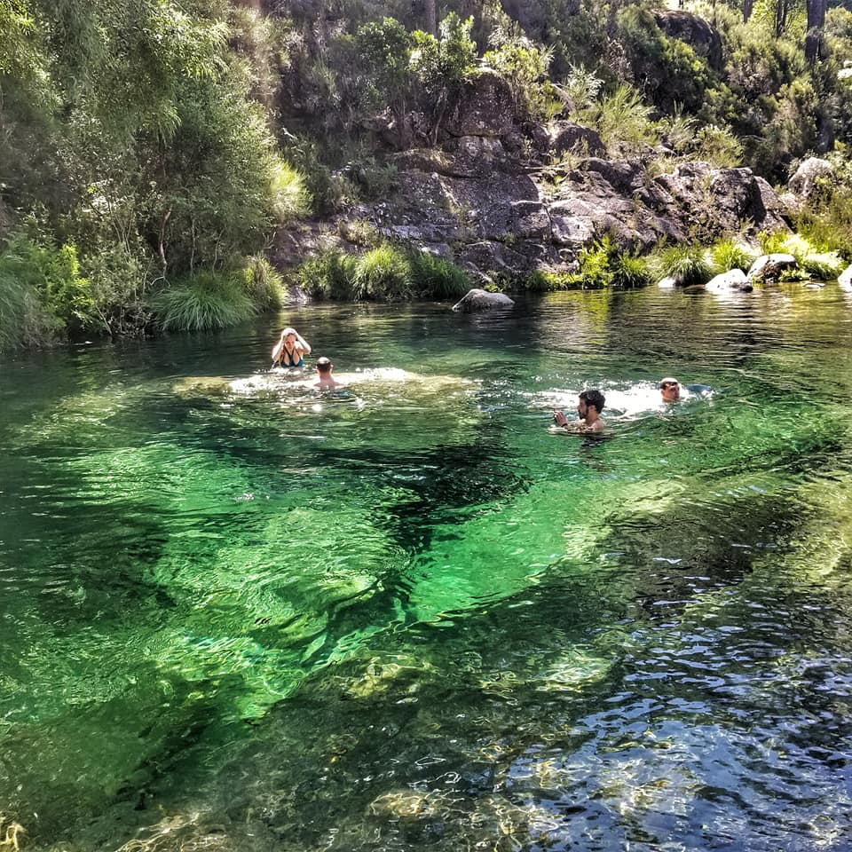 People swimming in crystal clear lagoon in Portuguese mountains.
