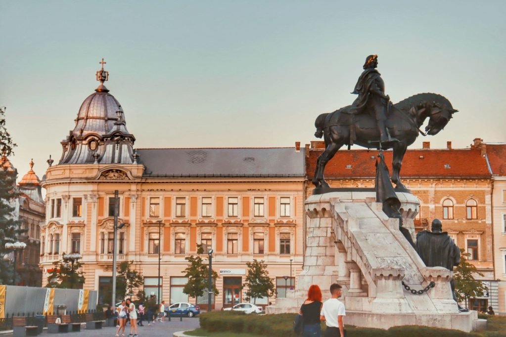 Union Square in Cluj-Napoca, Romania with a large silver domed building and a statue of a man on a horse.
