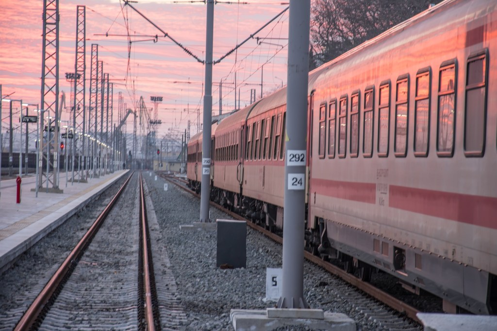 Train on tracks in Europe in pink sunset light.