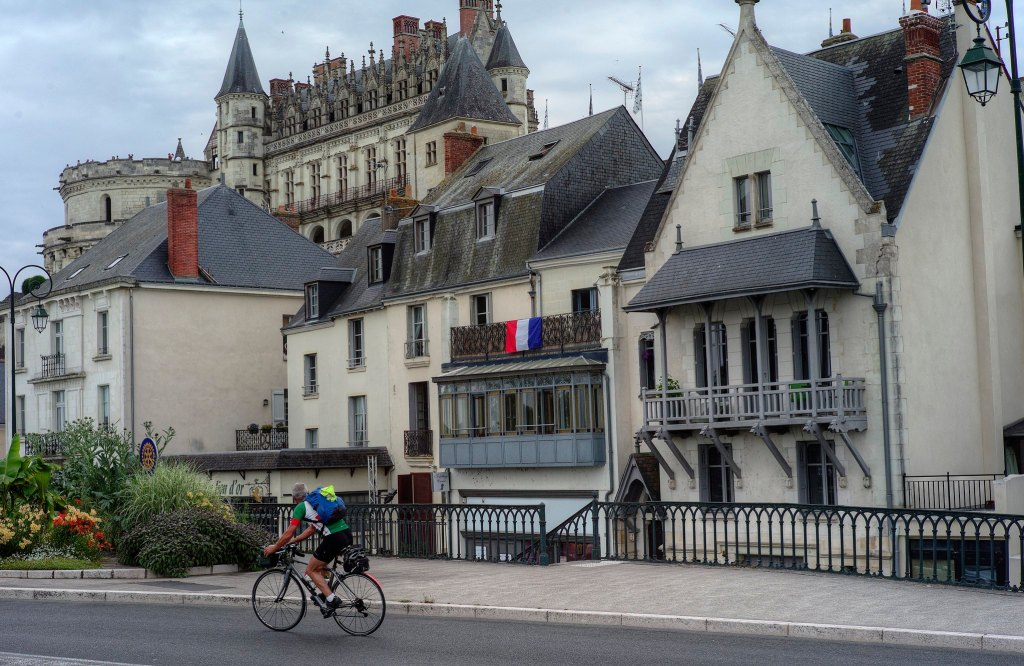 Man on bicycle in front of stone buildings in Amboise, France.