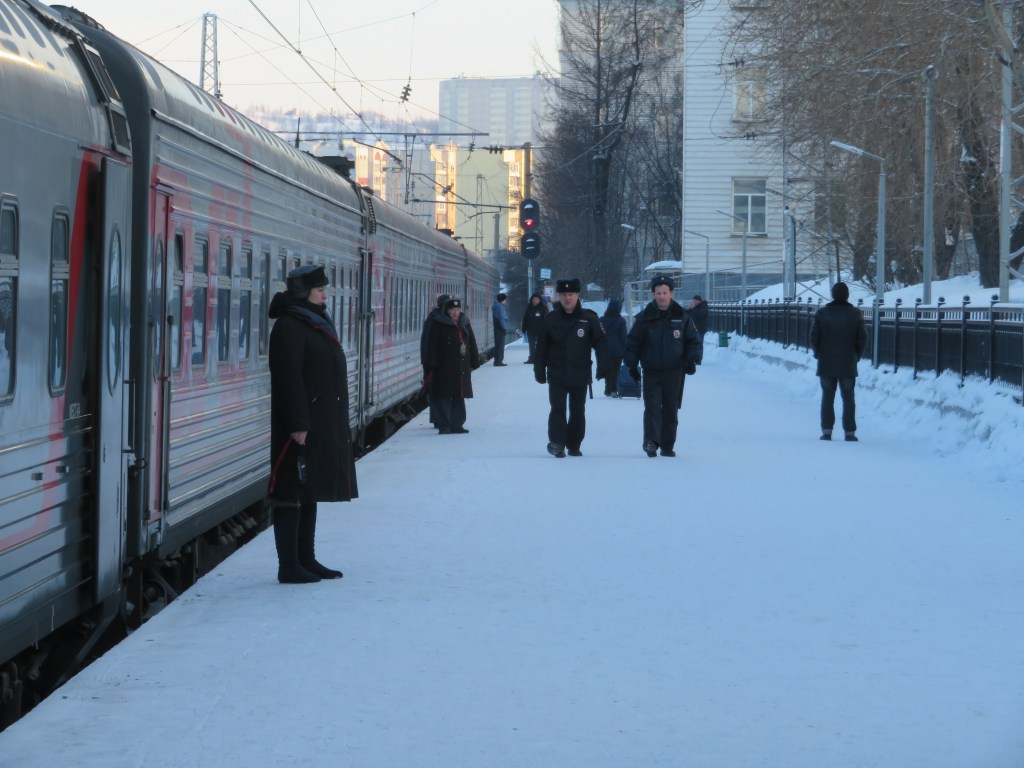 Russian train waiting to depart with officers outside in the snow.
