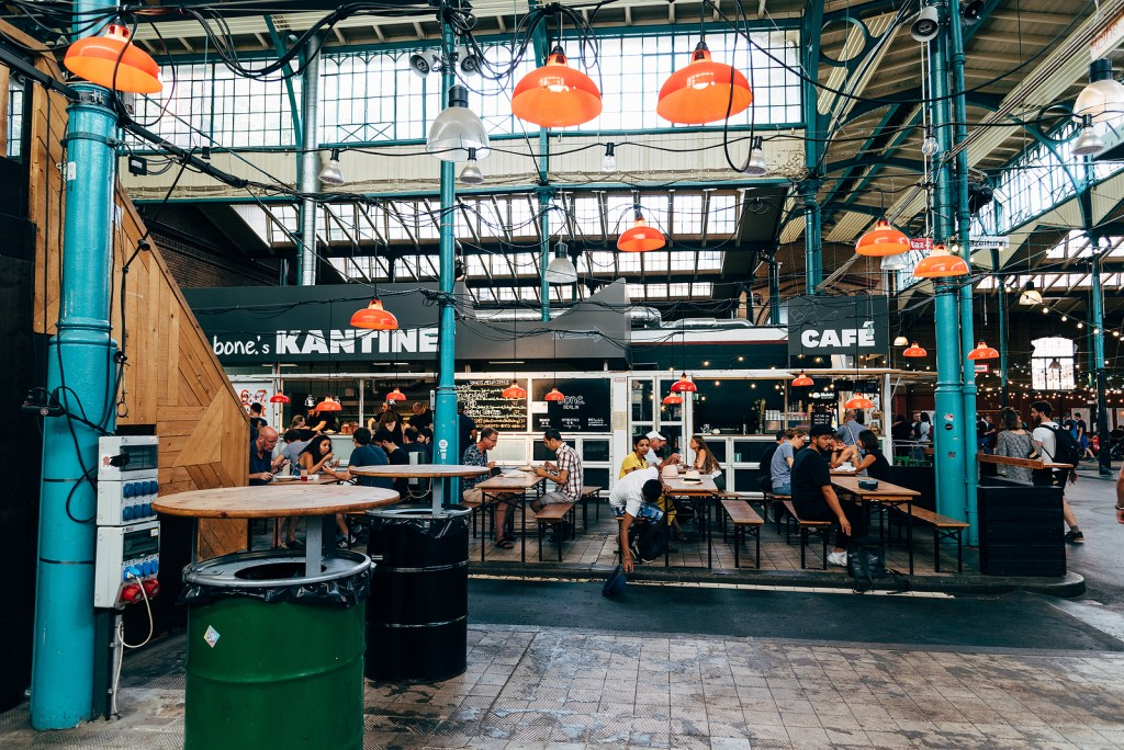 Markthalle IX interior in Berlin, Germany with tables and food vendors.