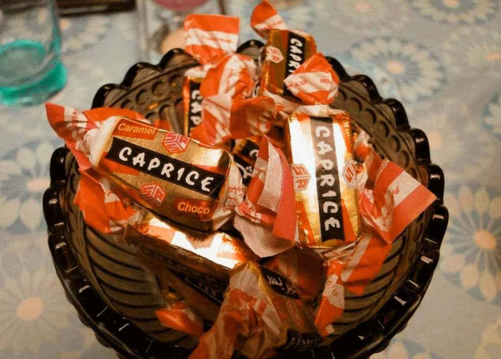 Bowl filled with individually wrapped Caprice candy from Algeria on a table.