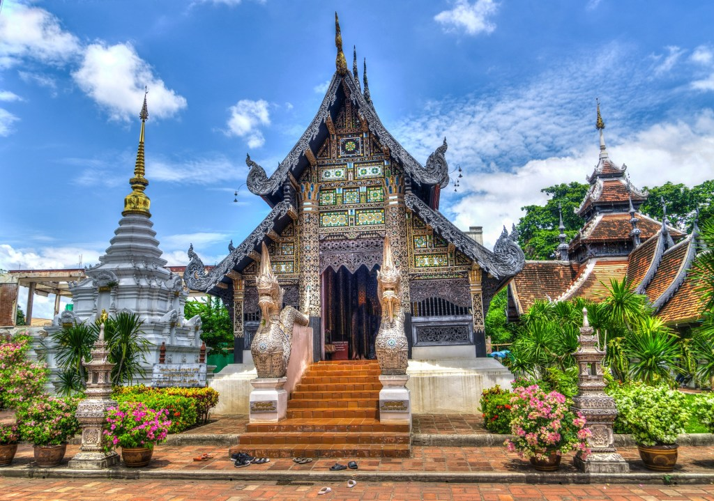Beautiful traditional building in Chiang Mai, Thailand surrounded by plants.