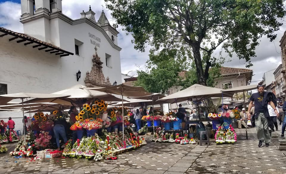 Open air flower market in Cueca, Ecuador with many stalls and people shopping.