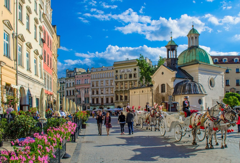 Krakow city center with a horse drawn carriage and flowers outside of the buildings.