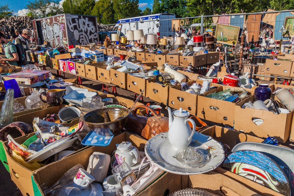 Table filled with assorted used items at Mauerpark Flea Market in Berlin, Germany.