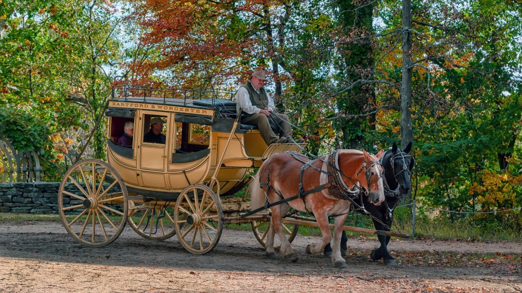 Horse and carriage in Old Sturbridge Village, Massachusetts.  The leaves are just beginning to turn yellow and orange as fall arrives.
