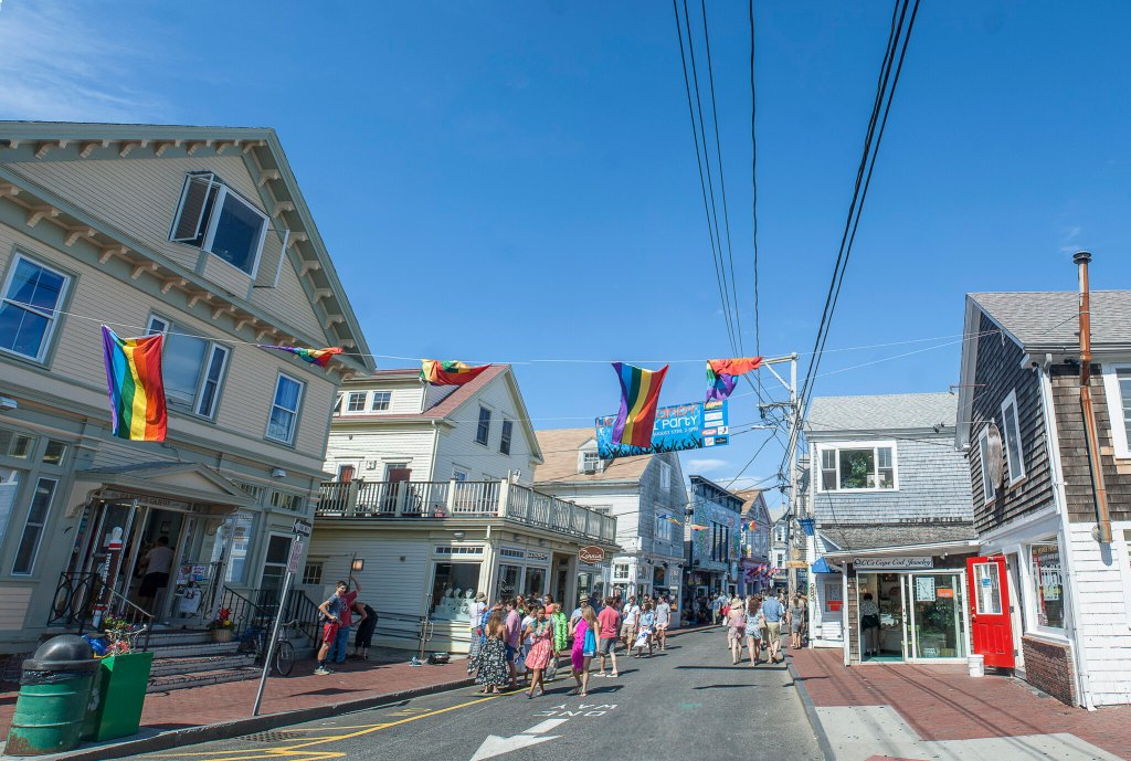 People walking around the streets of Provincetown, Massachusetts with rainbow flags flying across street posts.