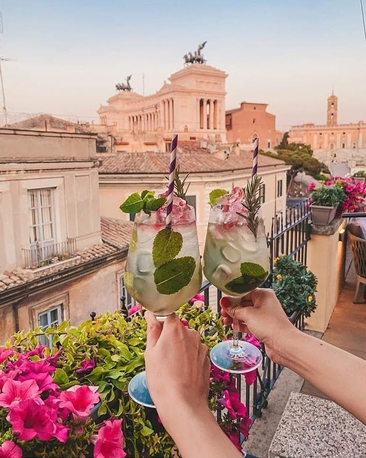 Two large wine glasses filled with a mixed drink and fruit with brightly colored straws being held up by two hands with Altare della Patria in the background.