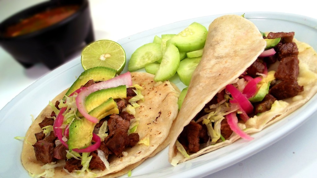Tacos filled with meat, avocado, and pickled red onion in soft corn tortillas.