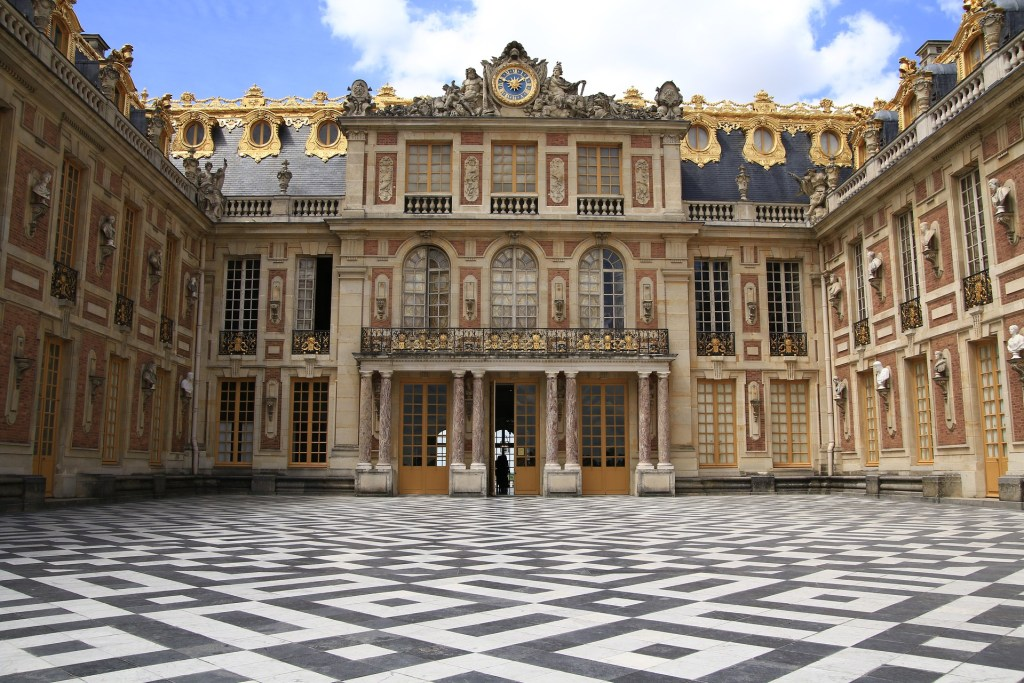 Palace of Versailles with iconic black and white tilework in the courtyard.