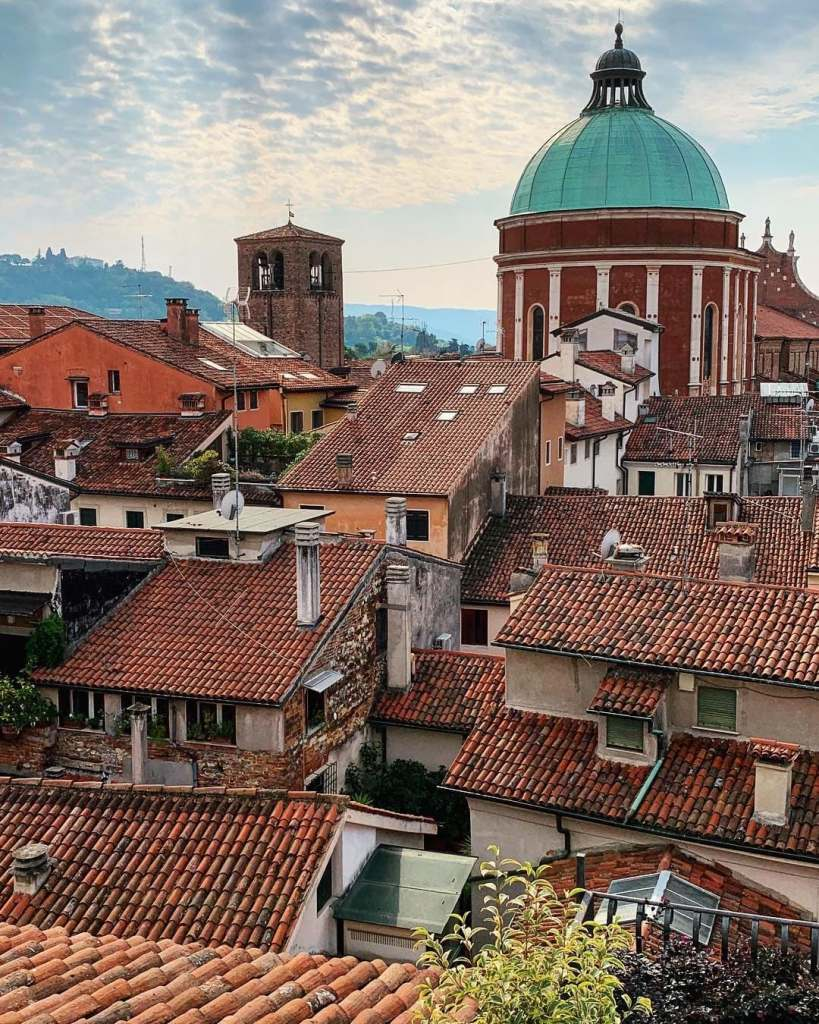 Blue dome of the Vicenza cathedral seen with many red tiled roofs in the Northeastern Italian city.