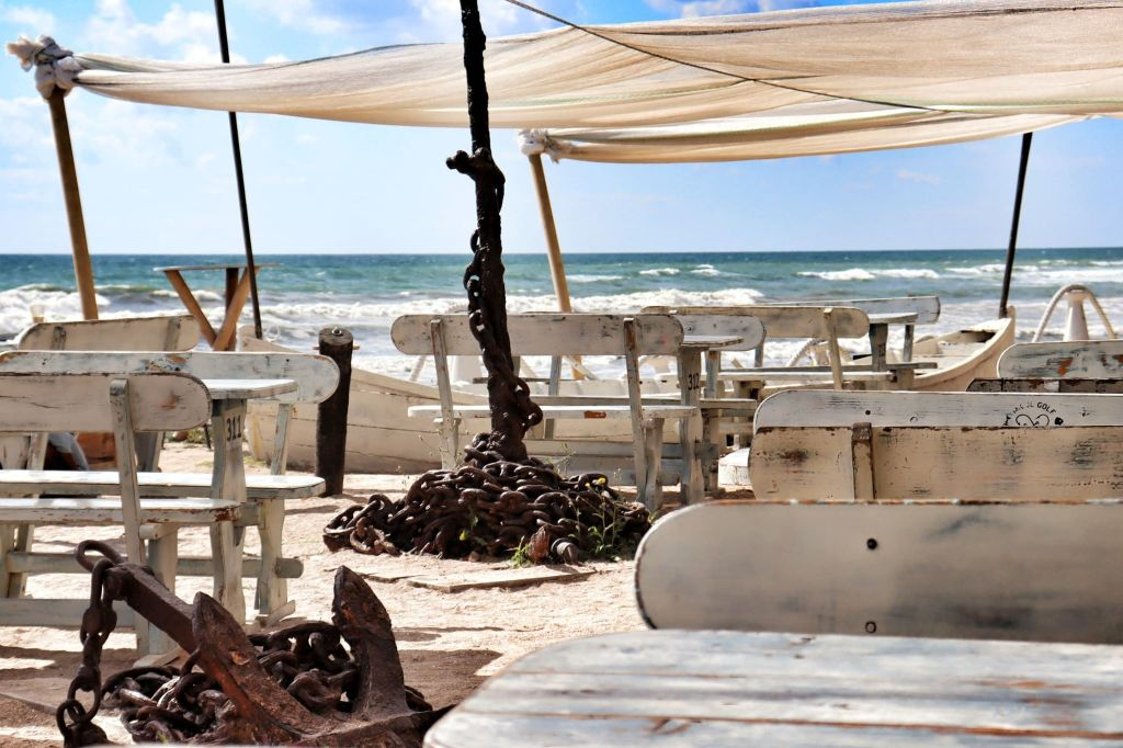 Empty tables next to the black sea with big white canopies shading the tables from the sun