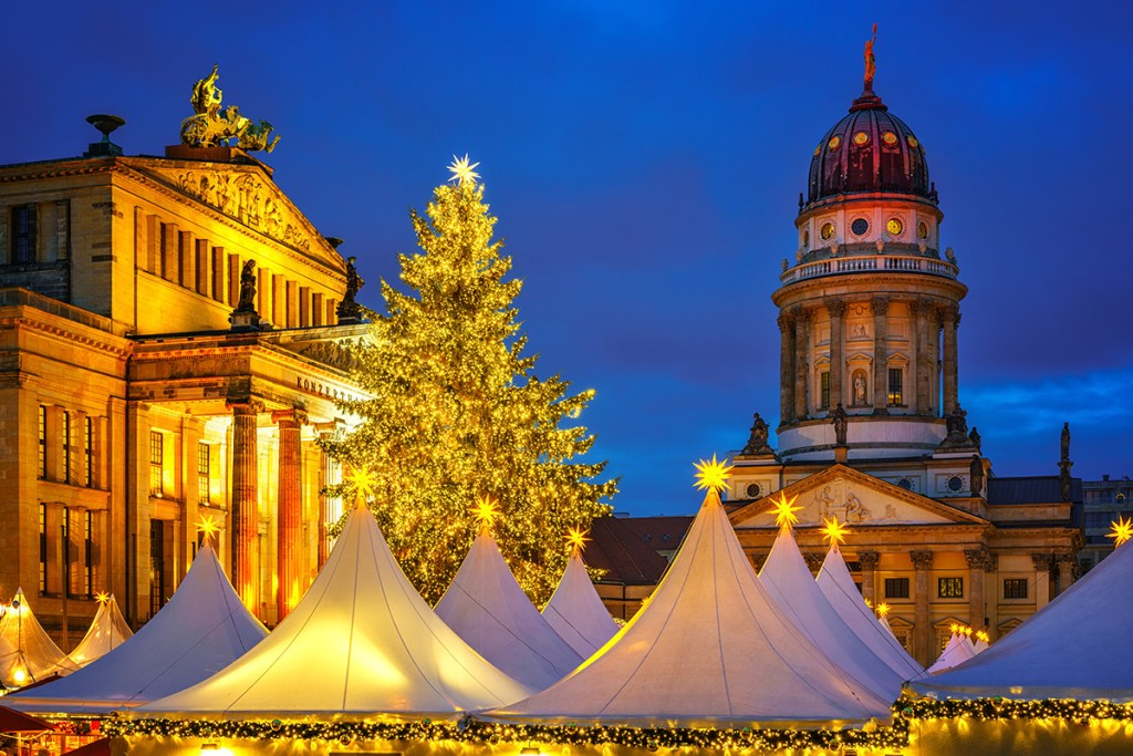 Under the iconic architecture of Berlin, white conical tents topped with golden stars are shown at night during this magical Christmas market.