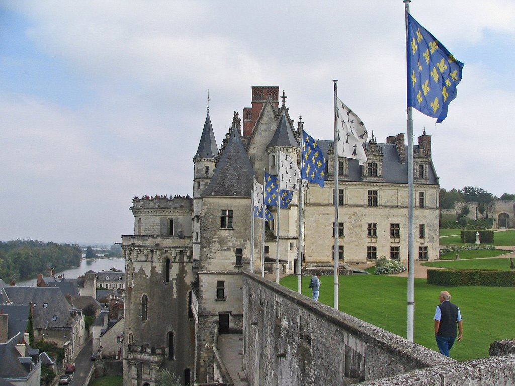 Chateau Royal d'Amboise seen from the side with manicured gardens and hedges in the background.