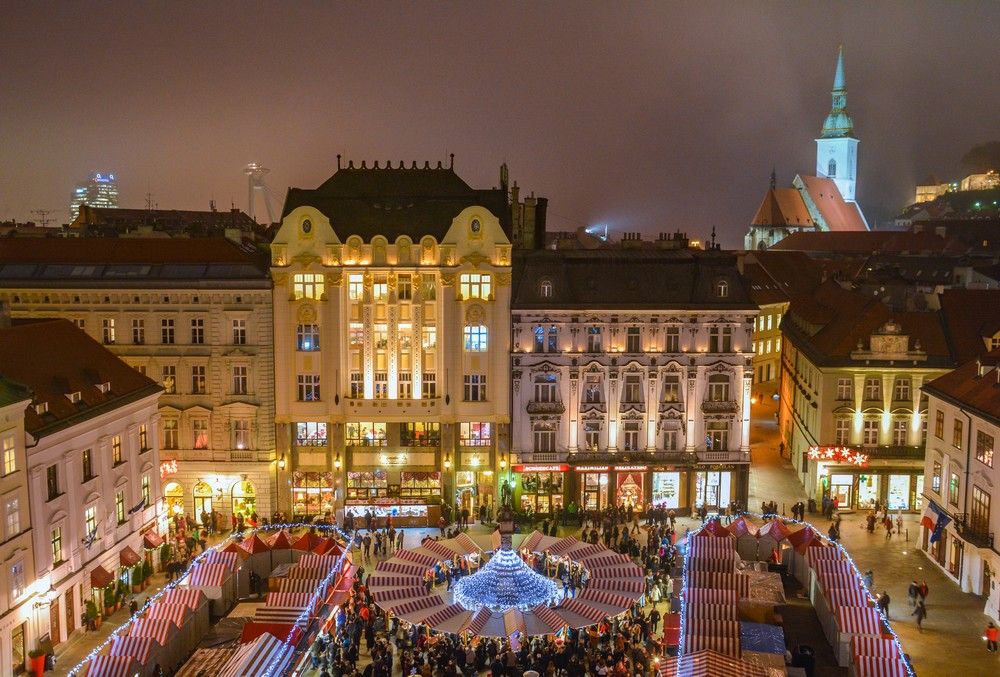 Aeriall view of an outdoor Slovak Christmas market in the capital of Bratislava.  It is night and the buildings are glowing with gold light as people stop at the different booths.