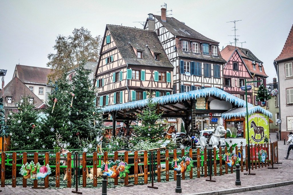 Half-timbered houses in Colmar, France are set in the background.  In the foreground, a Christmas carousel and decorated Christmas trees are on display during the town's Christmas market.